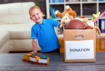 59157572 - boy taking donation box full with stuff for donate