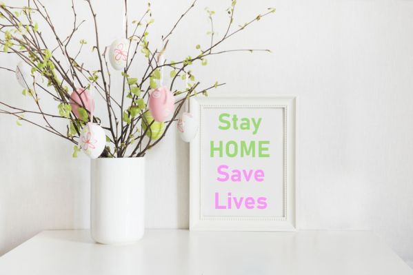 Easter concept 2020. Vase with birch tree branches with Easter eggs and frame with slogan - Stay at Home, Save Lives.